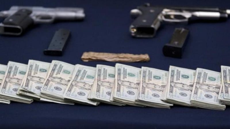 Officials also seized assault rifles, bundles of money, weapons and drugs [AP]