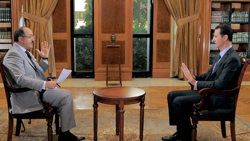President Bashar al-Assad (right) speaking during a television interview [EPA]