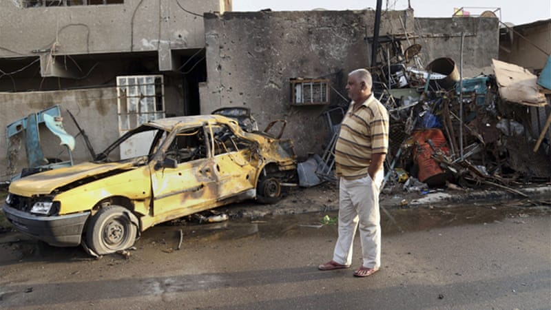 Iraqi man inspects his car destroyed in a suicide blast in Baghdad al-Jadidah district on Friday. [AP]