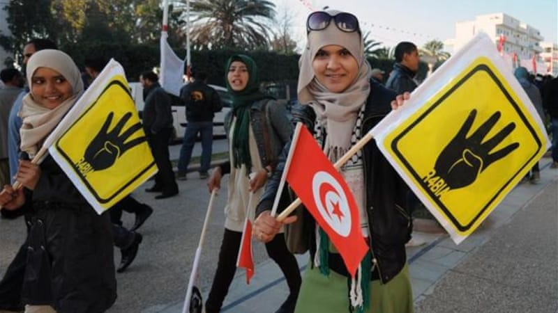 The new iconography of the Arab Spring includes the rabi'a in Egypt and black banners of Salafis in Tunisia [AFP]
