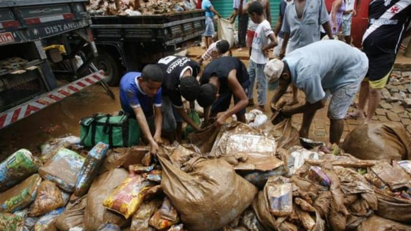 People have collected discarded food drenched in mud and rain from a supermarket in Espirito Santo state [AP]