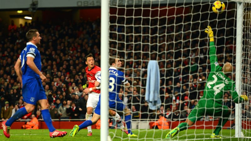 Mesut Oezil scores  Arsenal's goal past Everton's Tim Howard at Emirates Stadium in London [Getty Images]