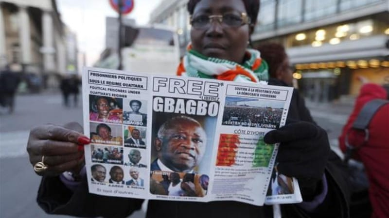 Pro-Gbagbo supporter holds a newspaper bearing the former Ivory Coast president's image ahead of his trial. (AFP)