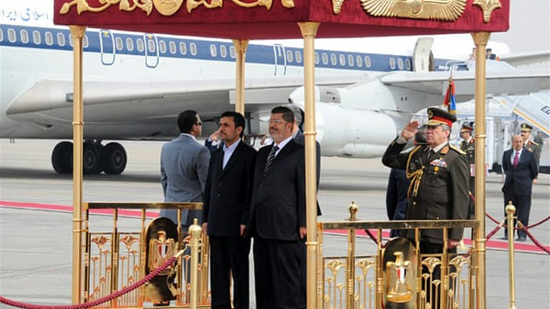 Egyptian security guards have arrested man who tried to hit Iranian President Ahmadinejad, left, with a shoe [AFP]