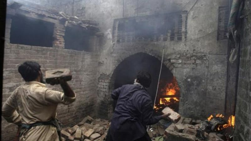 Angry protesters threw bricks at Christian houses after setting them on fire in Lahore [AP]