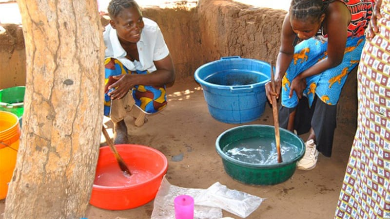 Women in Zambia mix jatropha oil with water and caustic soda to prepare soap [Dan van der Horst/Solutions Journal]