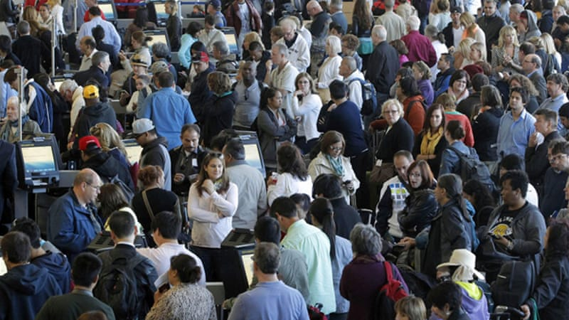 Passengers gather at the American Airlines check-in for flights at Los Angeles International Airport on Tuesday [AP]