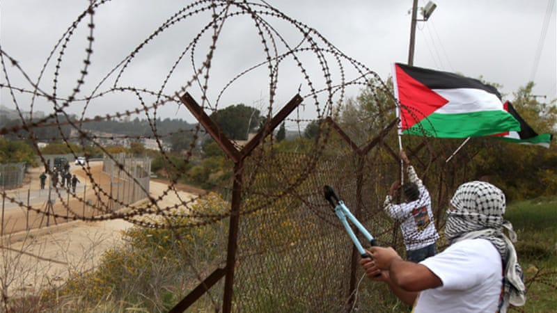 A protester cuts barbed wire on a fence between Jerusalem and Ramallah to mark Palestinian Prisoner Day [AFP]