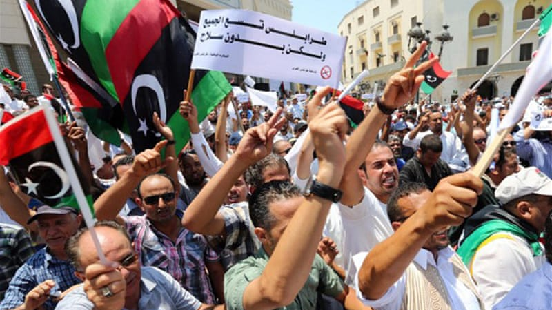 Libyan protesters have asked the government to remove arms and dismantle militia groups. [AFP]