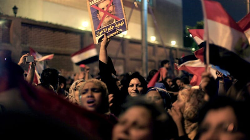 "A protester holds a poster that says, ""Tamarod, the end of the Muslim Brotherhood's regime,""  in Cairo, June 30 [AP]"