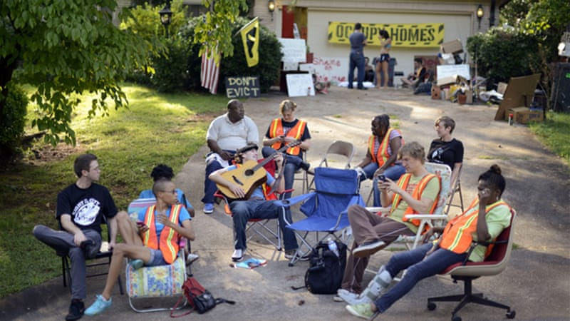 A group from Occupy Our Homes Atlanta camp overnight in the front yard of a foreclosed home [EPA]