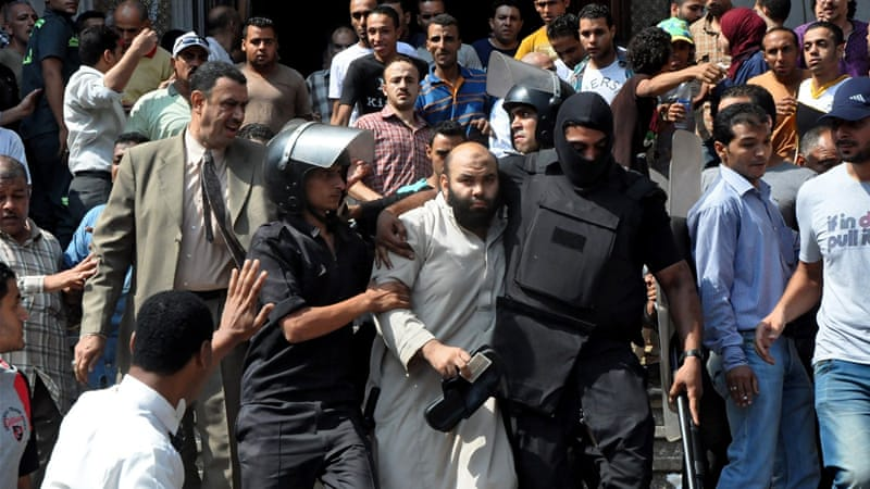Egyptian security forces escort a man out of the Fateh mosque [AP]