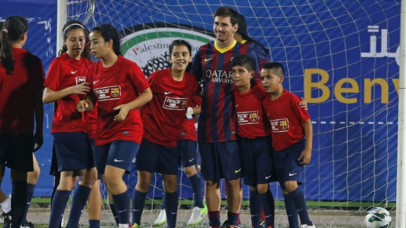 Messi poses for a photo with young Palestinian players in the West Bank [AP]