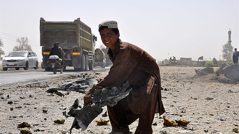 A child lifts a piece of mangled wreckage from a vehicle at the scene of the blast [AFP]