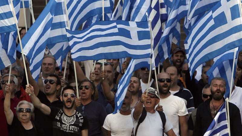 Supporters and members of extreme-right Golden Dawn party hold Greek national flags as they sing the national anthem outside the Greek police headquarters in Athens September 28, 2013 [Al Jazeera]