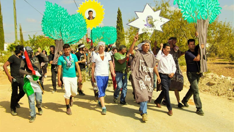 Marching through Bil'in towards the site of the parade celebrating culture and resistance [Creede Newton]