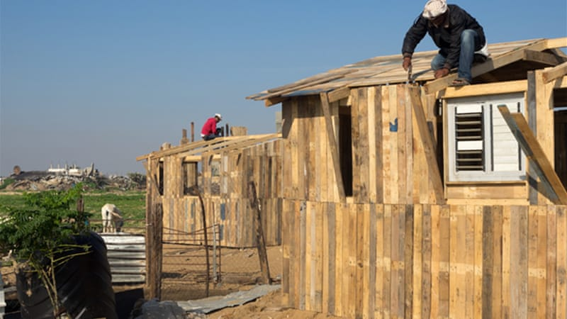 Workers have been using wooden pallets to construct temporary shelters in Beit Safiyya [Dan Cohen/Al Jazeera]