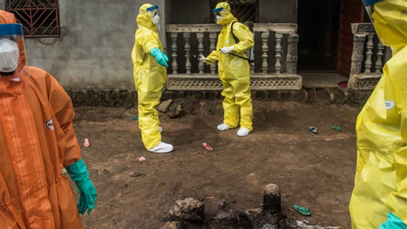 A burial team spray each other after picking up the body of a suspected Ebola victim [Tommy Trenchard/Al Jazeera]