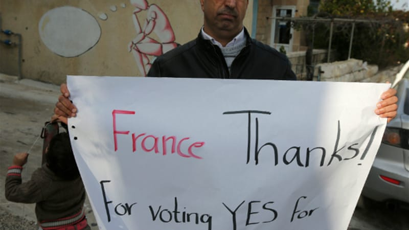 A Palestinian man holds a poster as he calls on France to vote for the recognition of a Palestinian state [AFP]