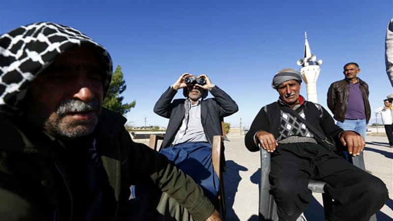 Turkish Kurds look at Syria from the roof of a mosque in Suruc [Reuters]
