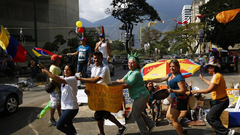 Anti-government protesters, dressed as Carnival revellers, stage a demonstration in Caracas [Reuters]