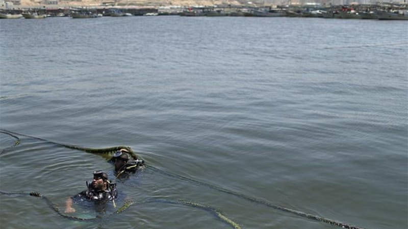 Palestinian divers inspected the boat after the explosion caused by an unknown party [Reuters]