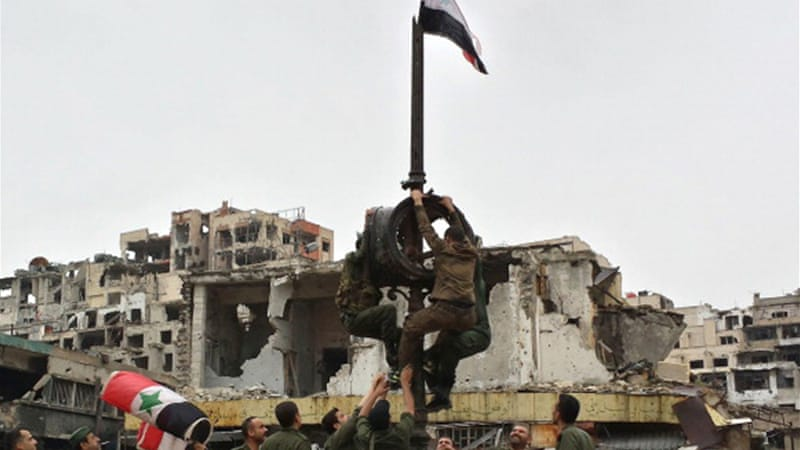 Syrian forces flew the national flag in central Homs [Getty]