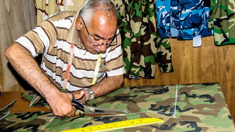 Tailor Abu Mohammad said he makes more than 35 military uniforms each day [Ridha Al Shammry/Al Jazeera]