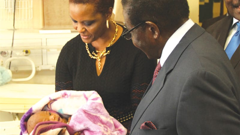 Mugabe and his wife Grace look at one of the twins at Harare Hospital [Gift Phiri/Al Jazeera]