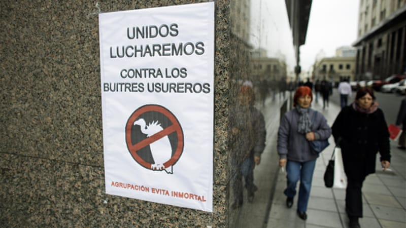 People in Buenos Aires walk past a sign saying: 'Together we will fight against the loan shark vultures' [AP]