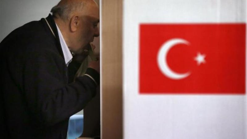 A man from Australia's Turkish community licks an envelope containing his vote at a Sydney polling booth [Reuters]