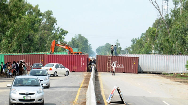 Pakistan's police have placed shipping containers across roads to block the march to Islamabad  [EPA]