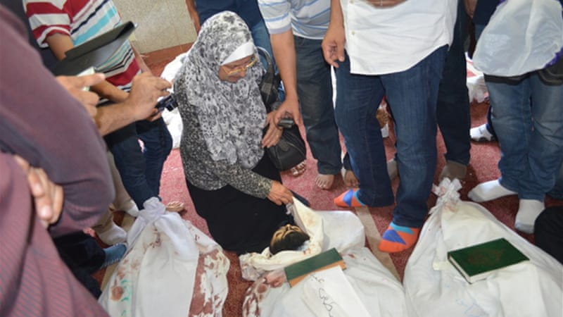 Amir's mother identifies her son among the bodies at a makeshift morgue [Ahmed Bedier/Al Jazeera]