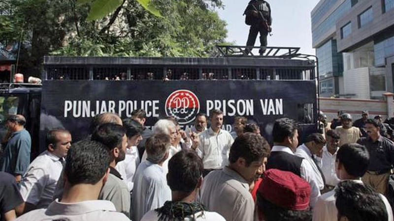 Anti-government activists gather to block prison van carrying their detained colleagues in Islamabad [AP]
