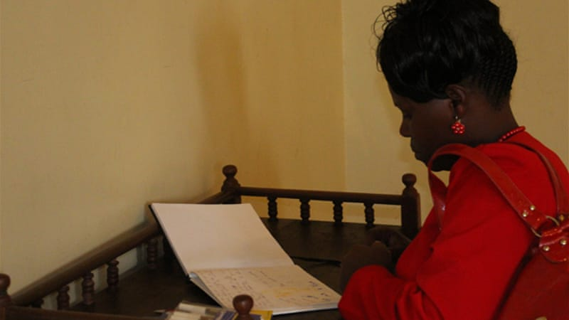 Charity Irungu, 43, reads a message she wrote in a remembrance book [Mohammed Yusuf/Al Jazeera]