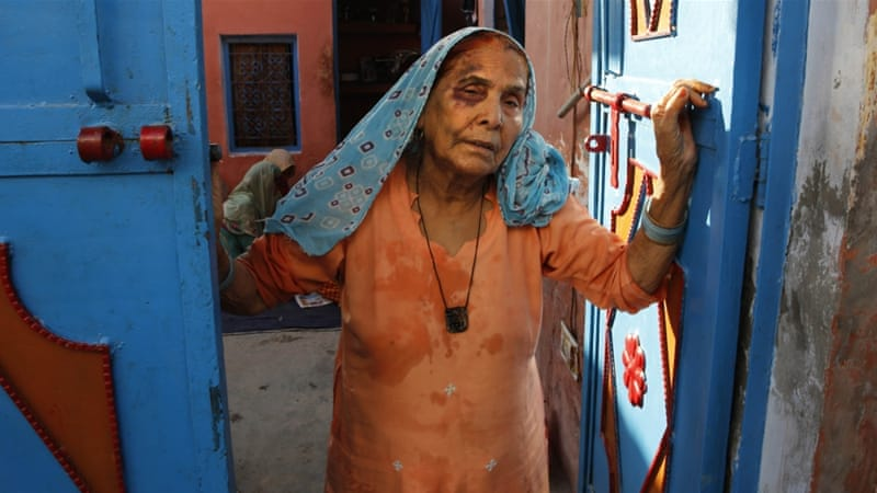 A bruised Asgari Begum, mother of the victim, stands by the entrance of her home in Bisara village [AP]