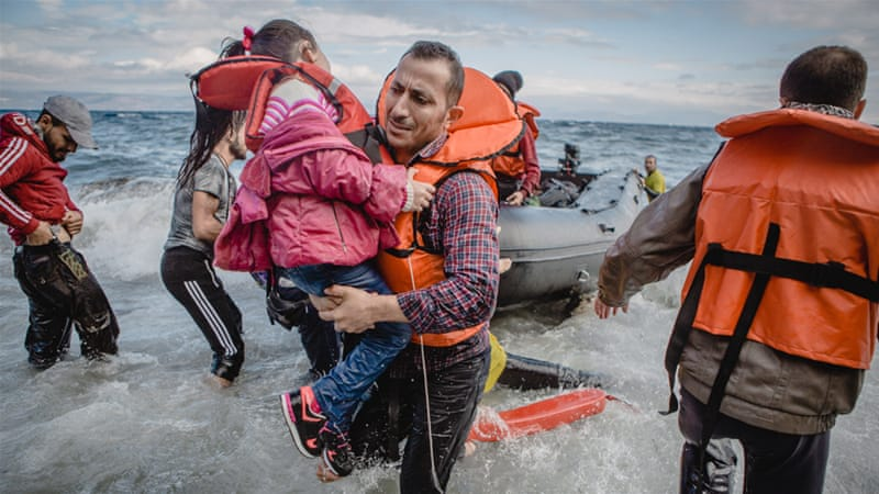 A father carries his daughter off their boat, which was stranded at sea for five hours, and on to the island of Lesbos. [Anna DiCenzo/Al Jazeera]