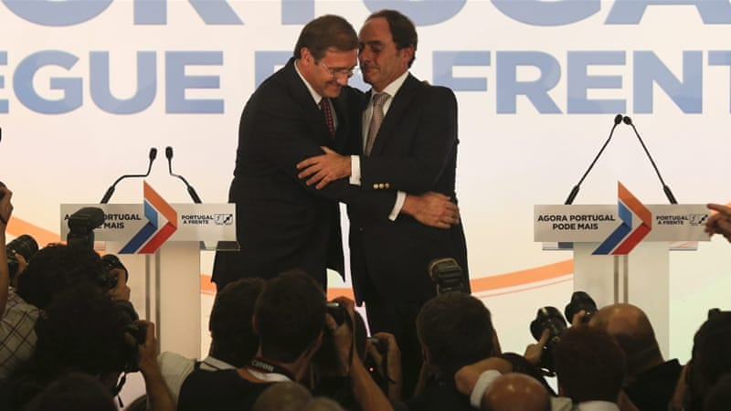 Coelho, left, and Popular Party President Paulo Portas congratulate each other during their victory speech in Lisbon [EPA]