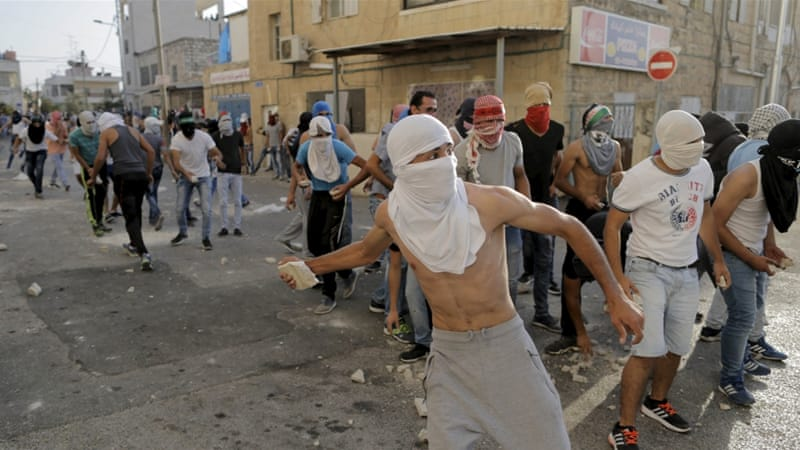 Palestinian protesters throw stones towards Israeli police during clashes in Shuafat, an Arab suburb of Jerusalem [REUTERS]
