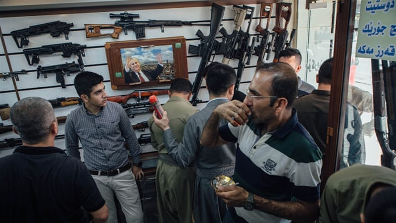 Customers crowd into a small gun shop in Sulaimania to drink tea and inspect guns for sale [Andrea DiCenzo/Al Jazeera]