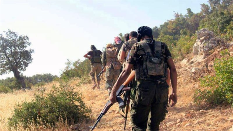 Syrian rebels walk towards army positions in the western Akrad mountain region in the coastal province of Latakia, Syria [AP]