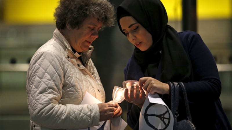 Two women light candles during an interfaith vigil for the victims of the Paris attacks in London, UK [REUTERS]