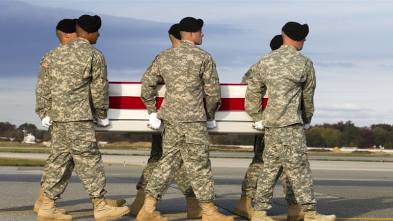 An army team carries the transfer case containing the remains of Army Master Sergeant Joshua L Wheeler [AP]