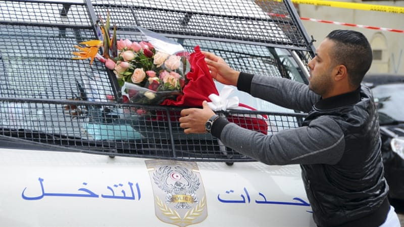 A man places a bouquet of flowers on a police van, near the bus that exploded Tuesday in Tunis [AP]