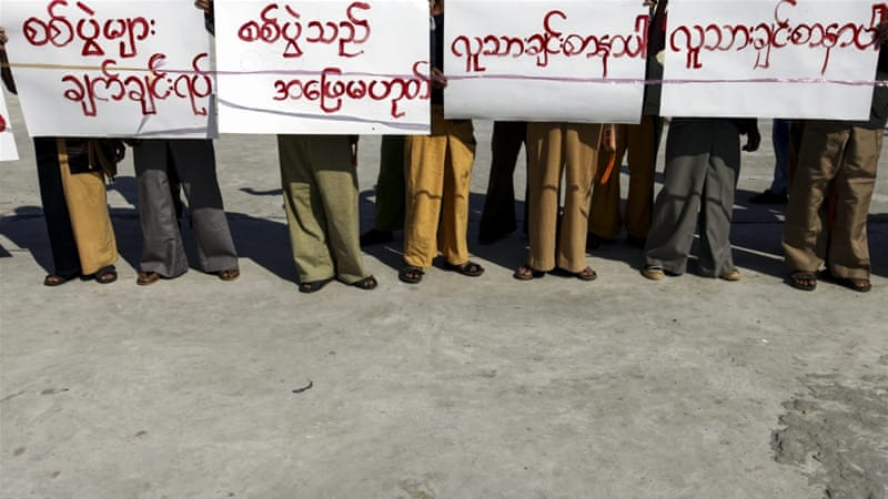 Demonstrators hold placards during a protest demanding a stop to military operations in the Mandalay area [EPA]