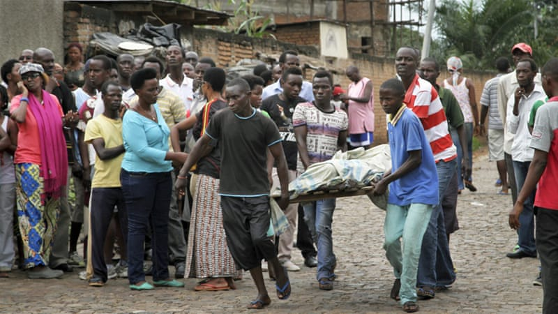 Men carry away a body in the Nyakabiga neighbourhood of Bujumbura, Burundi on Saturday [AP Photo]