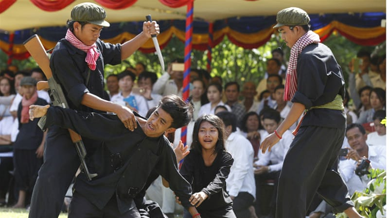 A scene from the notorious ''Killing Fields'' is re-enacted during a ceremony in Phnom Penh [Mak Remissa/EPA]