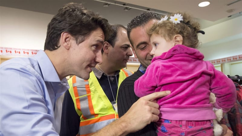 Prime Minister Justin Trudeau greets refugees fleeing Syria, during their arrival at Pearson International airport, Toronto [AP]