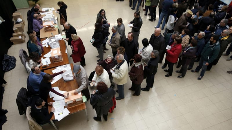 Voters in Barcelona queue at a polling station to cast ballots in Spain's general election [Albert Gea/Reuters]