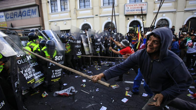 Demonstrators clash with riot police during protests against President Rafael Correa's rule [EPA]
